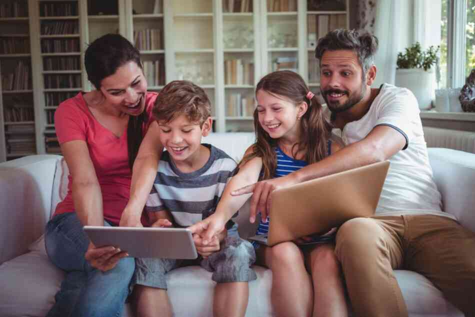 Family looking at laptop and tablet together