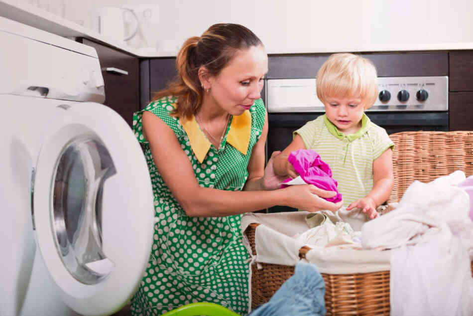 Mom doing laundry while toddler looks on