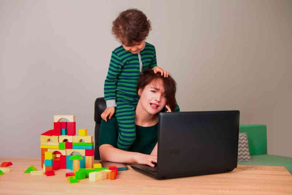 Toddler bothering mom at computer