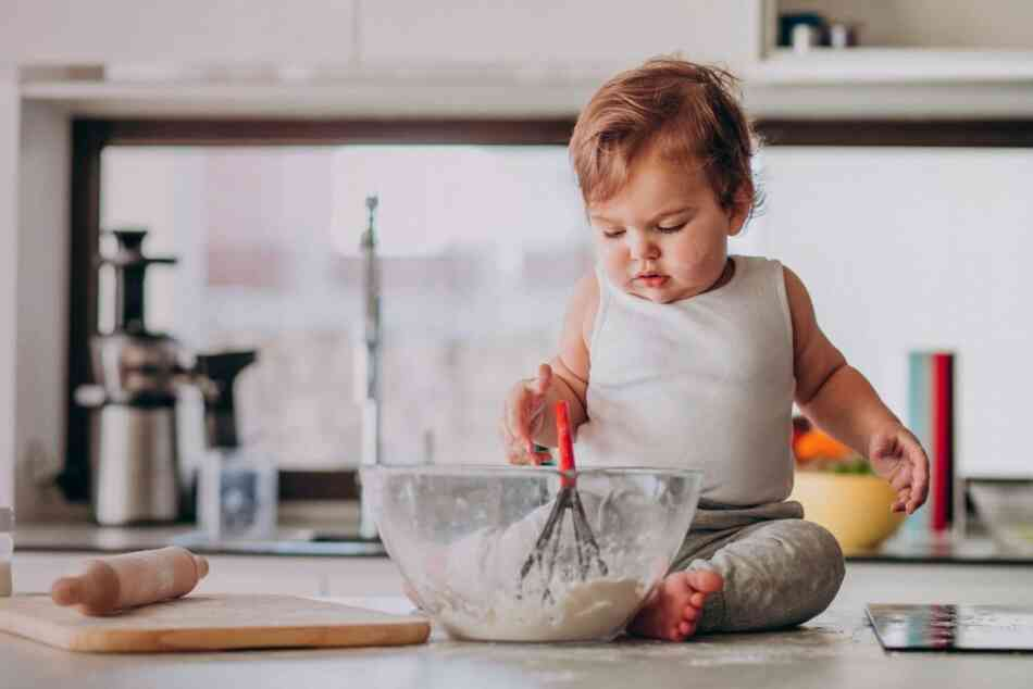 Toddler with whisk in kitchen