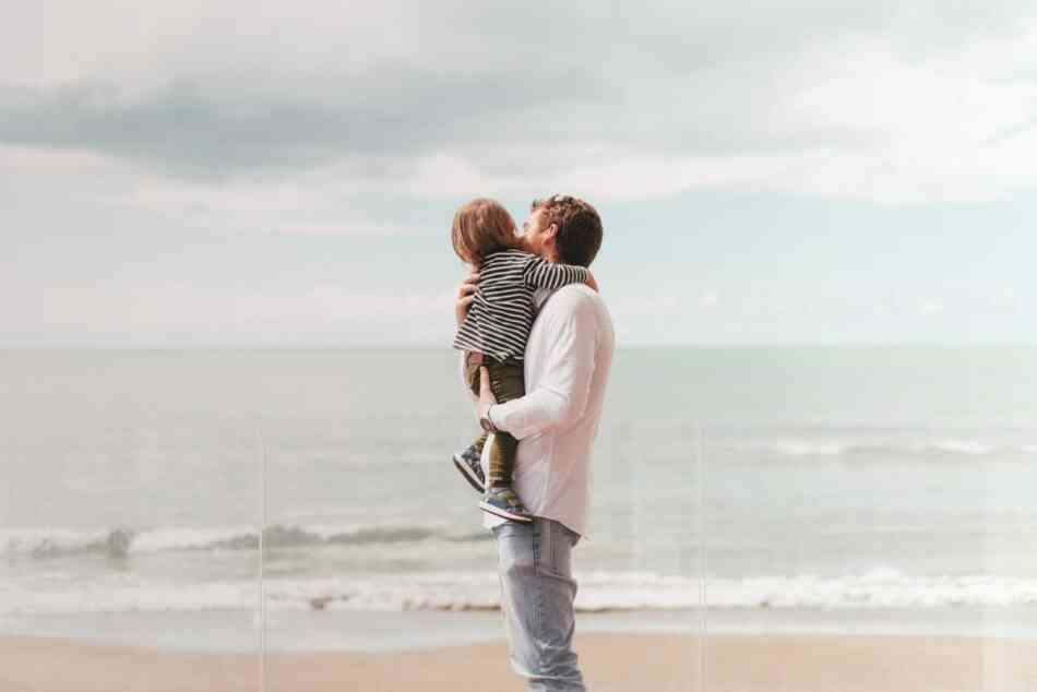 Father holding son on beach