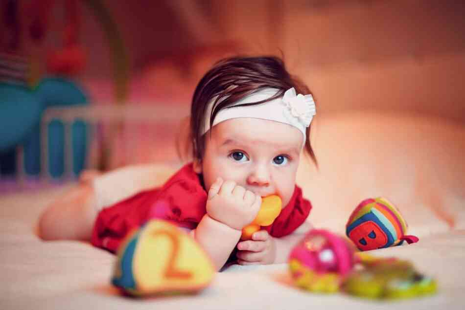 Baby putting toy in her mouth