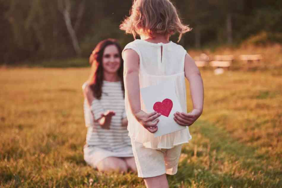 Daughter giving card to mom
