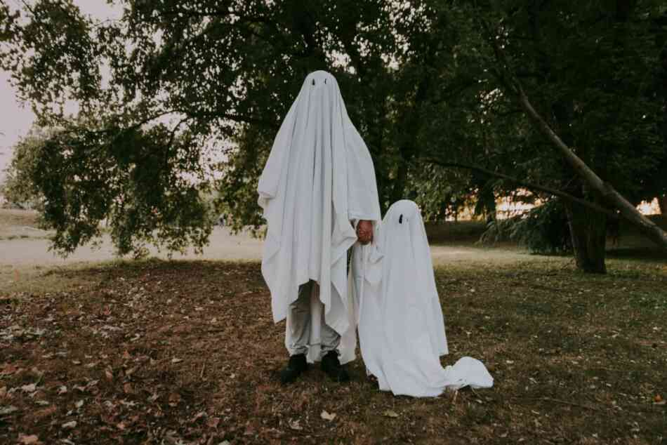 Parent and child dressed up as ghosts