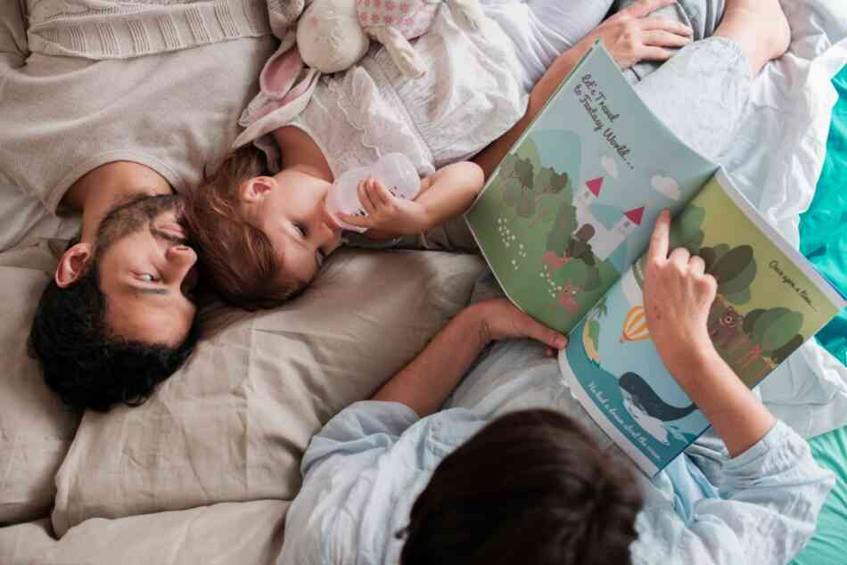 Parents reading to toddler in bed