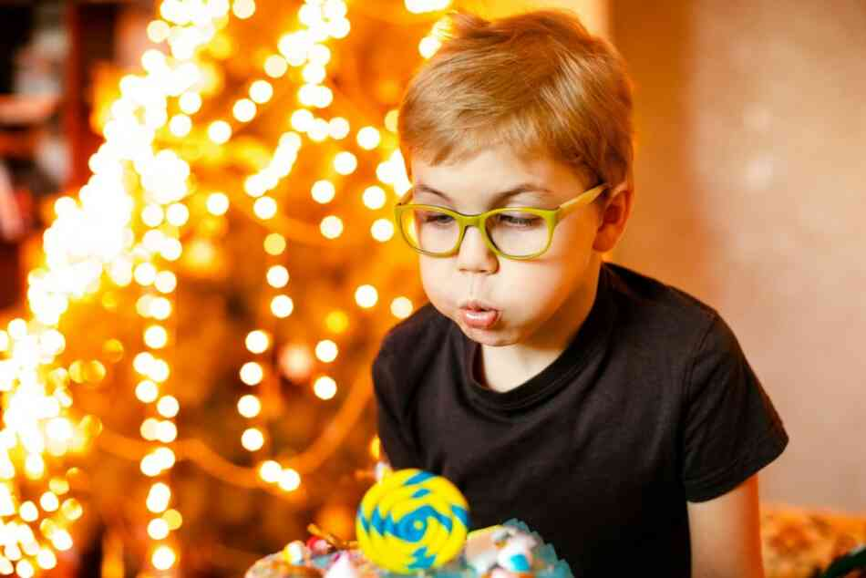 boy blowing out birthday candles in front of Christmas tree