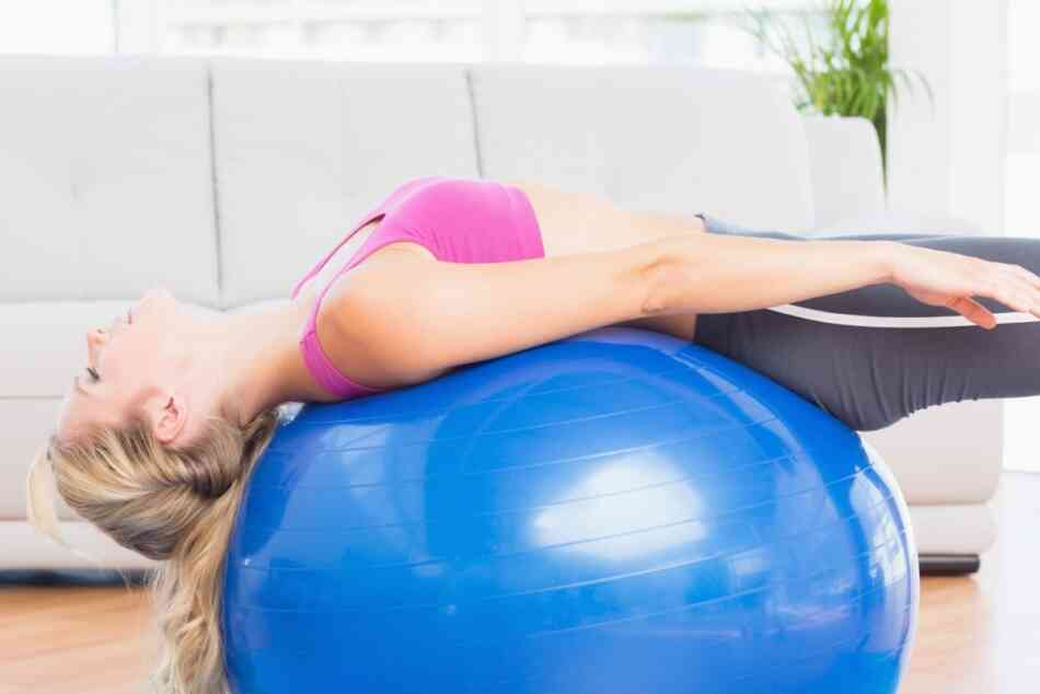 woman stretching her back on yoga exercise ball