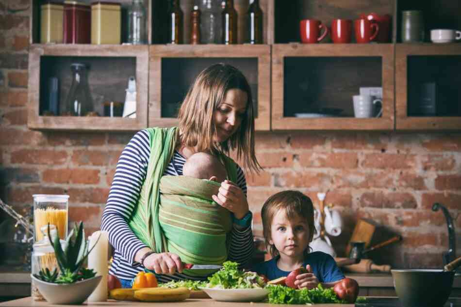 Baby wearing mom in kitchen