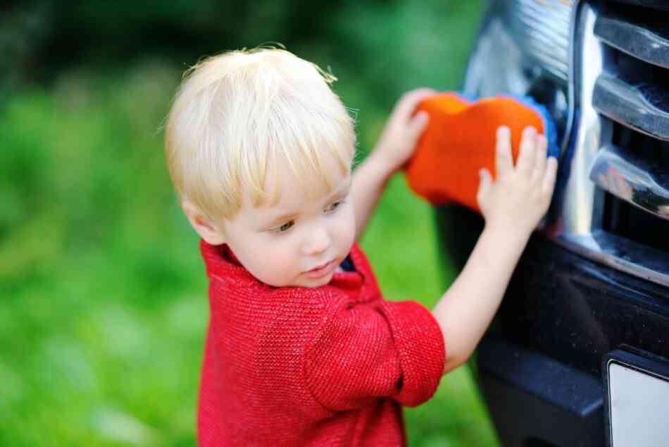 toddler experiments with sponge on dad's car