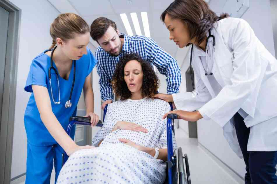 Pregnant woman in pain comforted by doctors and birth partner