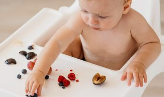 baby eats fruit in high chair