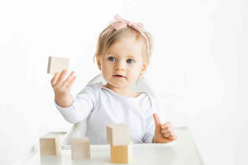 baby girl playing with wooden block