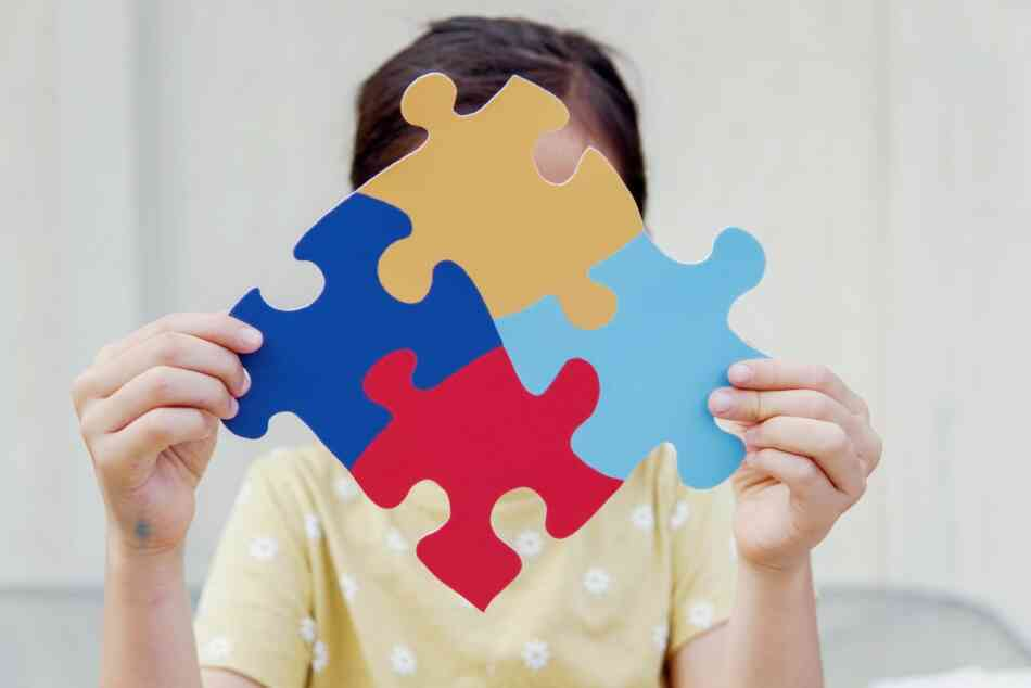 girl holds autism jigsaw