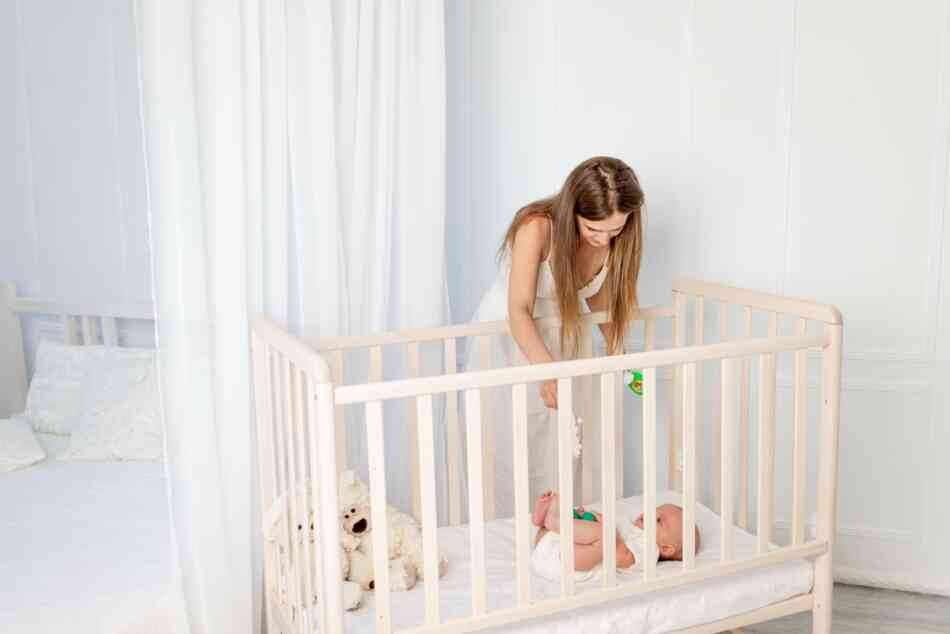 mom plays with baby in crib