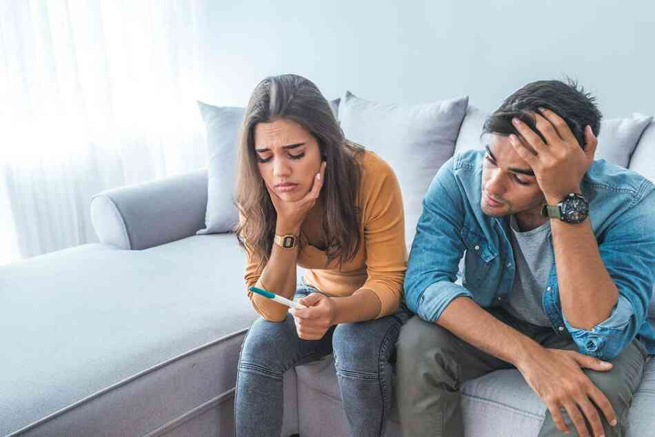 frustrated-couple-staring-at-pregnancy-test-result
