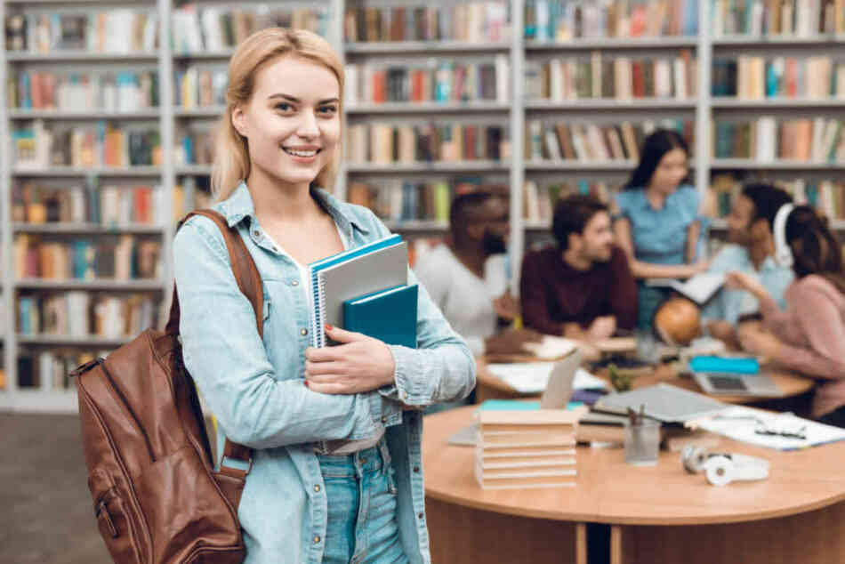college student in library with classmates