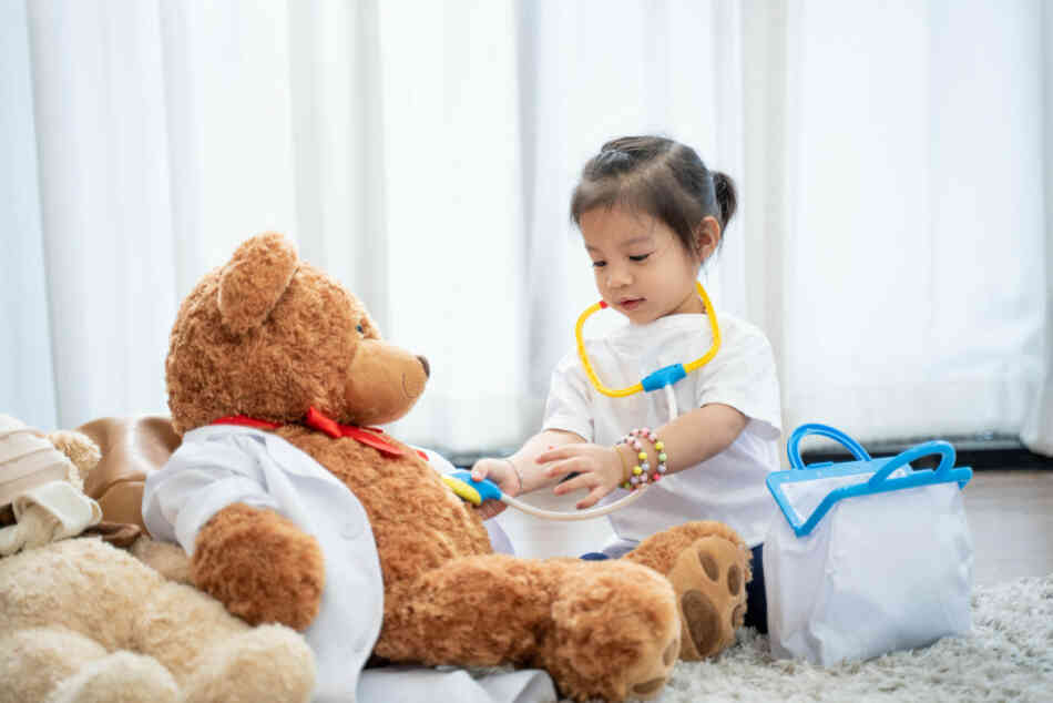 toddler playing doctor to toy
