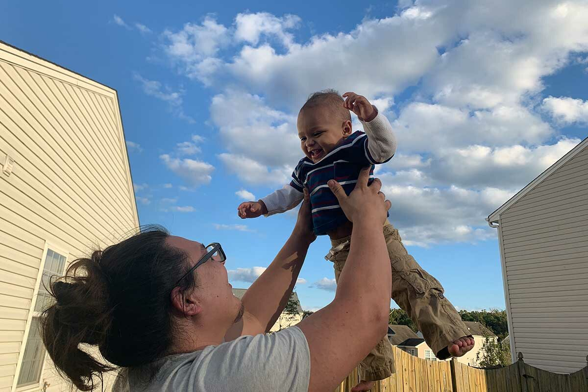 Mom tossing baby toddler in the air