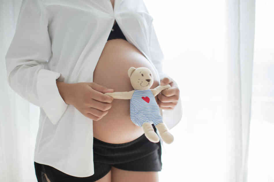 pregnant woman with teddy bear on belly