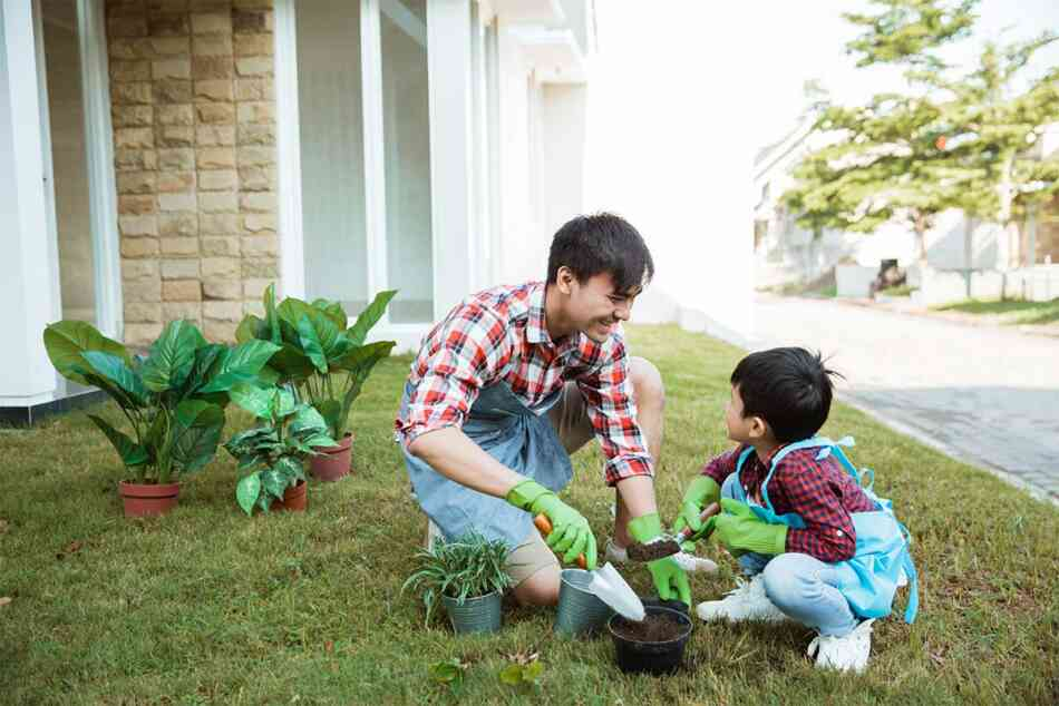 dad and son gardening outside their house