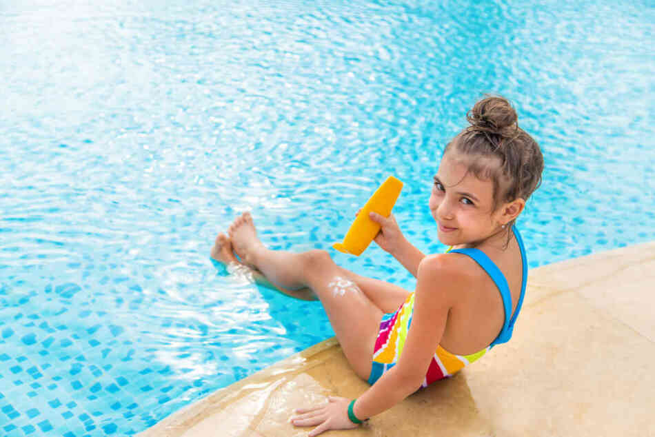little girl putting on sunscreen by the pool