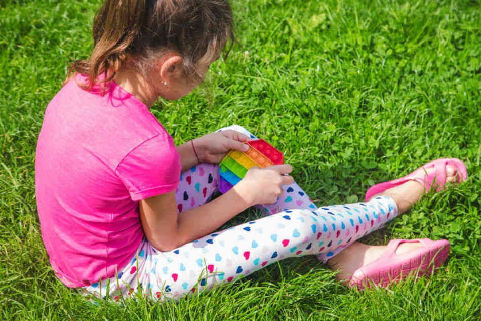 young girl playing with fidget sensory toy