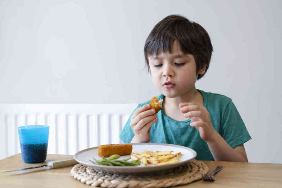 Portrait of 5 year old kid boy having homemade fish finger and f