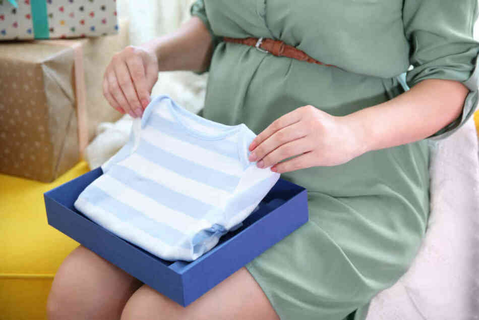 pregnant mom opening gifts at baby shower
