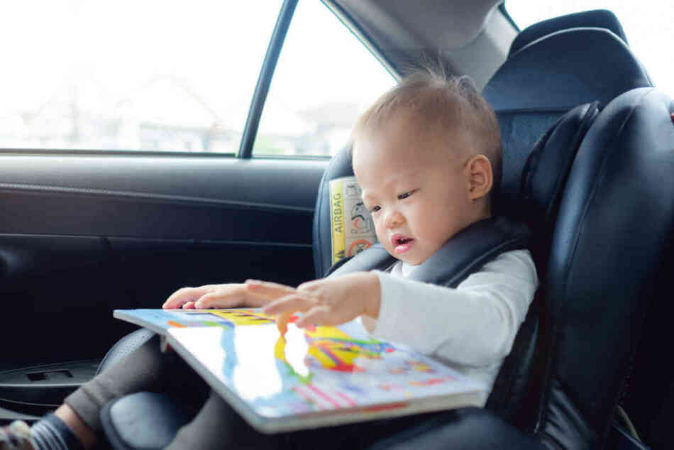 toddler enjoys reading a book in the car