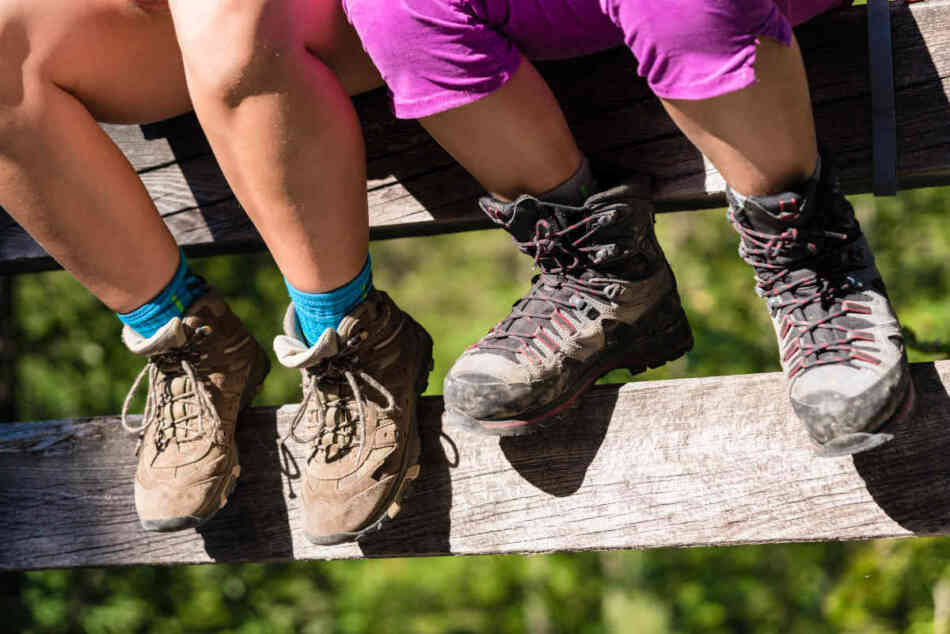Two children with hiking boots sitting on rail of bridge