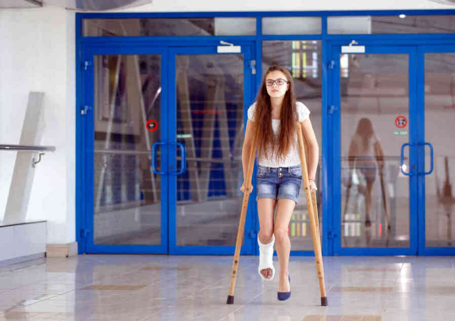 young girl injured during sports in crutches