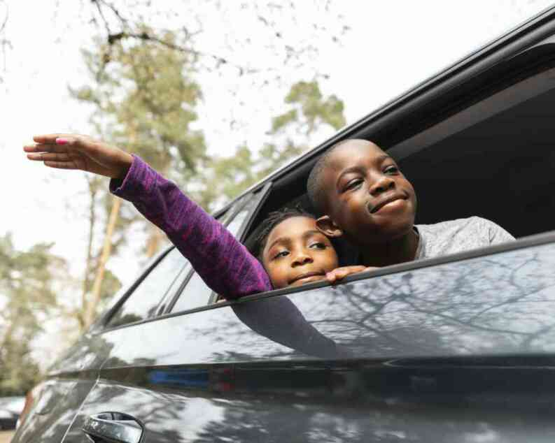two kids counting trees from car