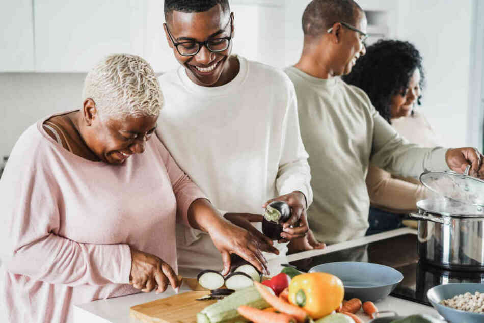 sandwich generation parents preparing dinner with their son and aging parent