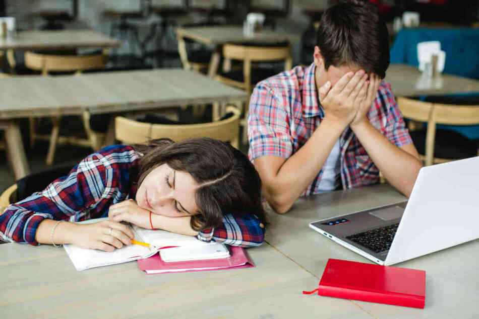 two students exhausted in class