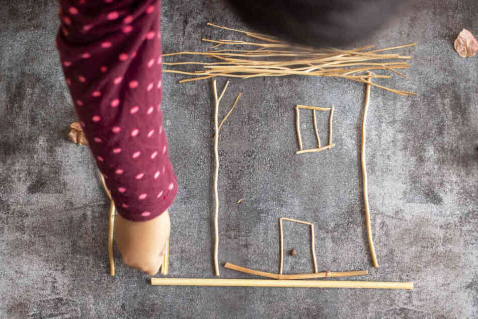 toddler enjoying loose parts play by building house with sprigs