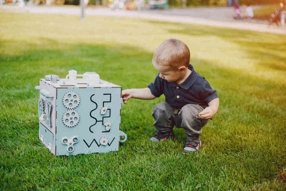 young boy playing with engineering toy