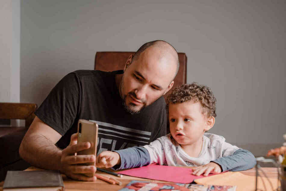 dad helps son check spelling on smartphone