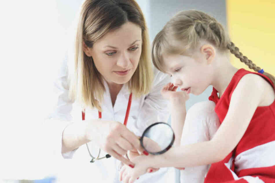 doctor examining young girl with skin rash on arm