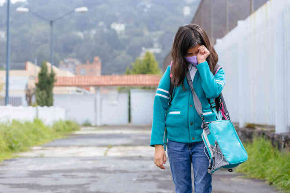 young kid reluctantly going to school