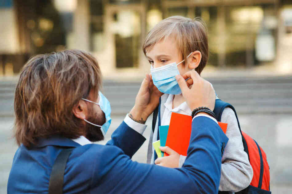 dad helping son put on face mask to school