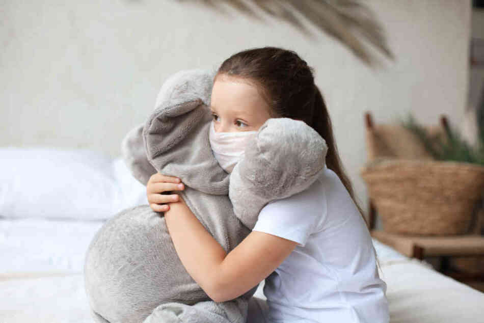 Young girl in mask hugging doll friend