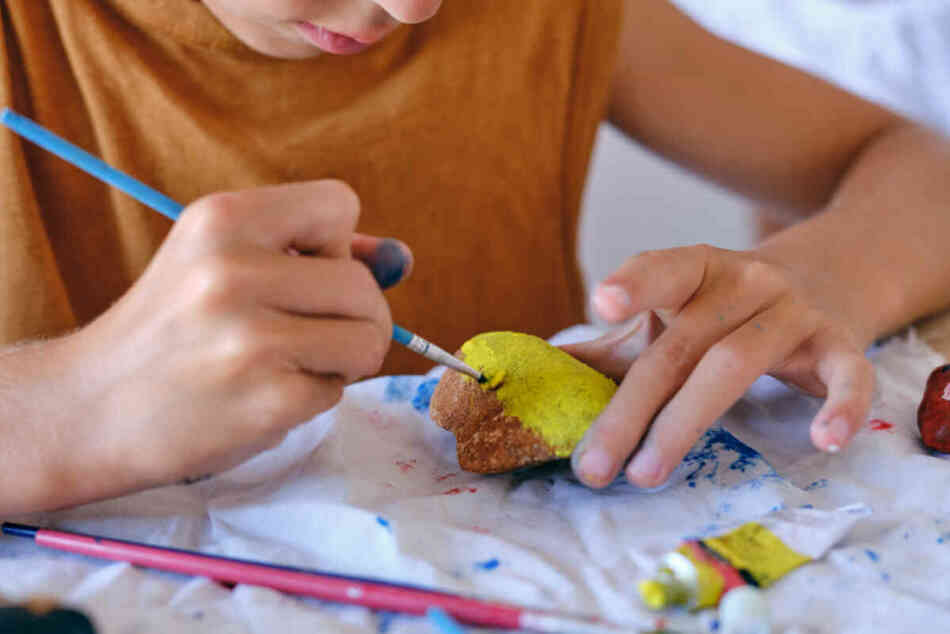 boy painting rocks at home