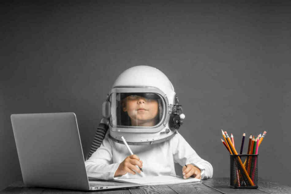 young boy reading while wearing an astronaut's helmet