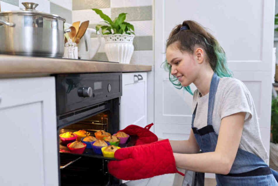 young teen girl baking cupcakes for family