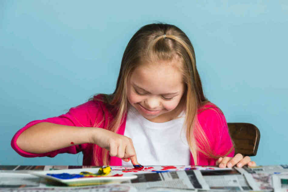young girl with down syndrome playing with paints